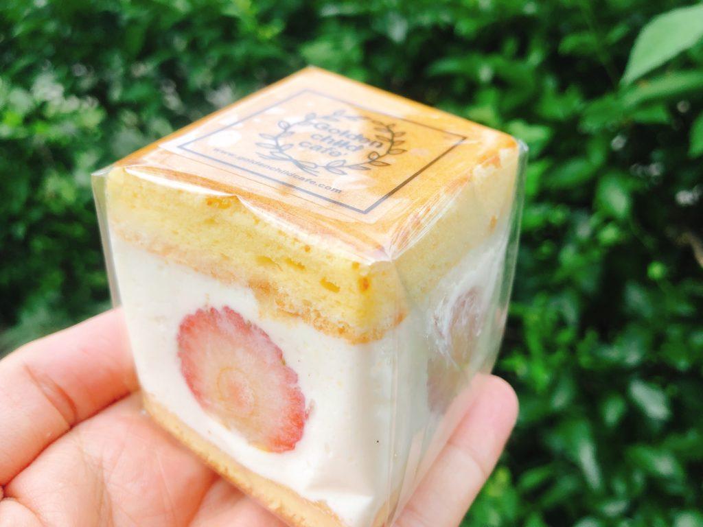 ゴルチャのフルーツサンド「cream box」のいちご(1個500円)を手の上に載せている